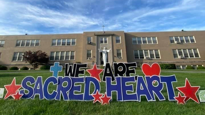A picture of our school with our hashtag We Are Sacred Heart